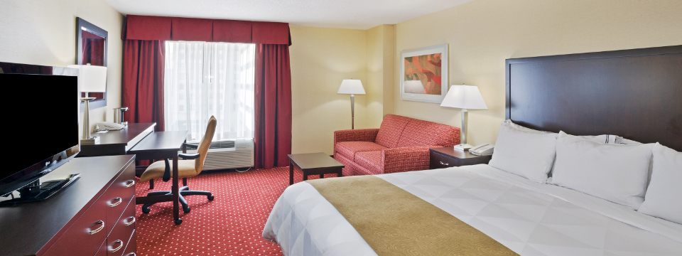 Hotel room with king bed and red sleeper sofa