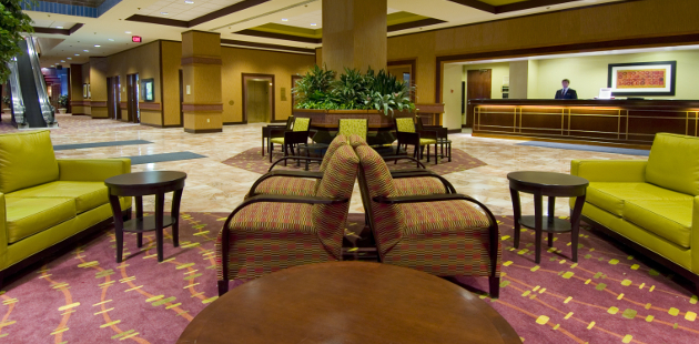 Seating area with green couches in hotel lobby
