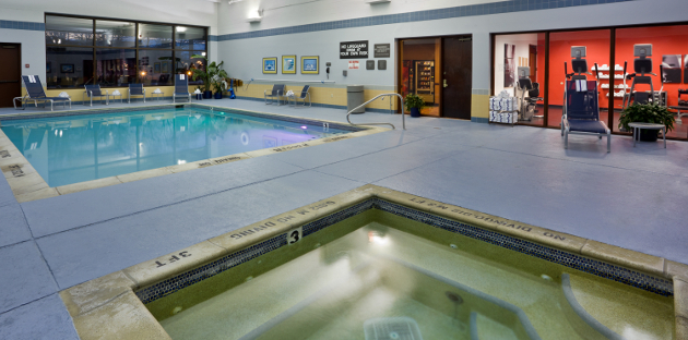 Hotel's rectangular indoor pool and hot tub beside fitness center