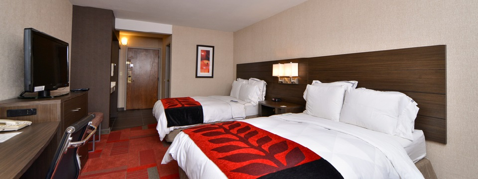 Hotel room furnished with two double beds