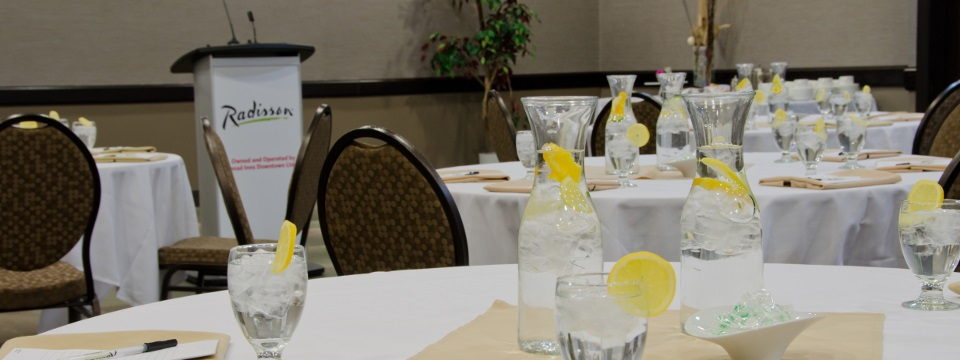 Round tables in white linens with ice water pitchers and water glasses