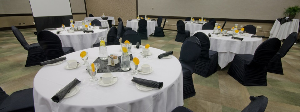 Meeting room with round tables covered in white linens with chairs in black linens