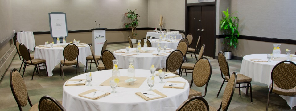 Hotel meeting room set with round tables in white linens with ice water pitchers and water glasses