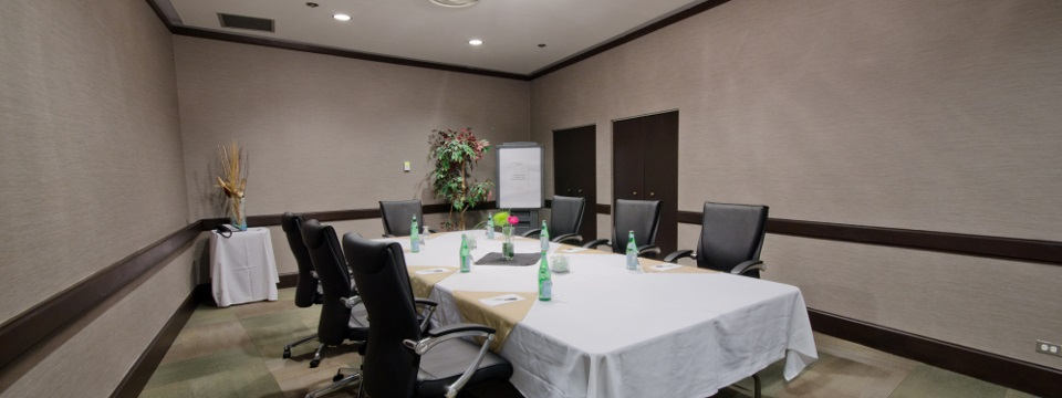 Meeting room with table covered in white linen with seven leather chairs