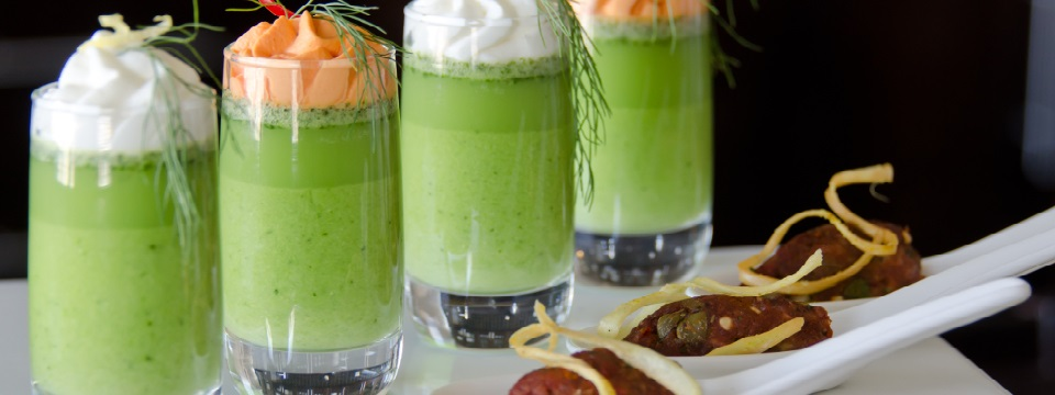 Four small aperitif glasses filled with green drink served with small appetizers