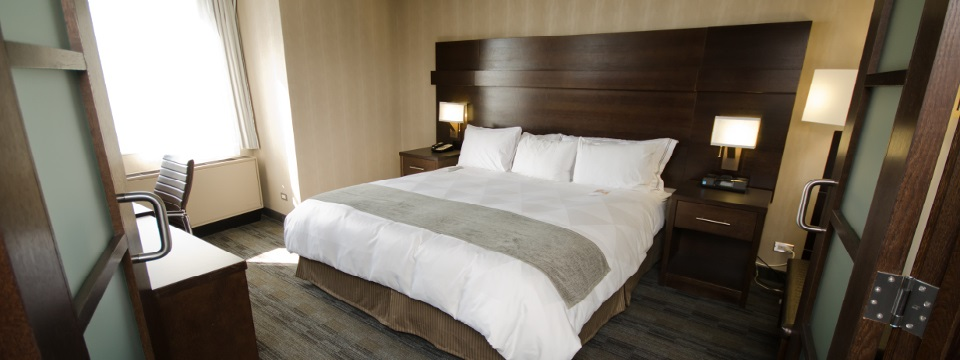 Hotel room with king bed against modern dark wood headboard with side tables