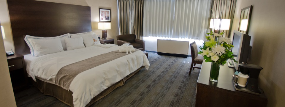 Hotel bedroom with king bed in white linens with dark wood headboard
