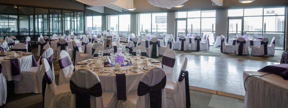 Reception space with natural light and round tables covered in white and purple linens