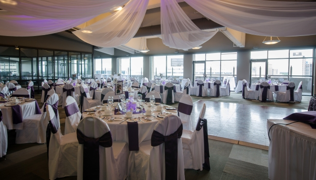 Event venue featuring round tables covered with white linens and purple bows