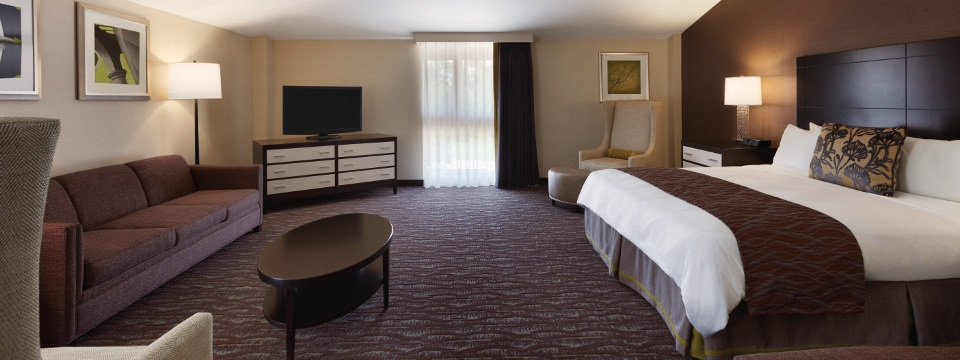 Suite's open floor plan includes king bed, sofa, side chair and dresser with flat-screen TV
