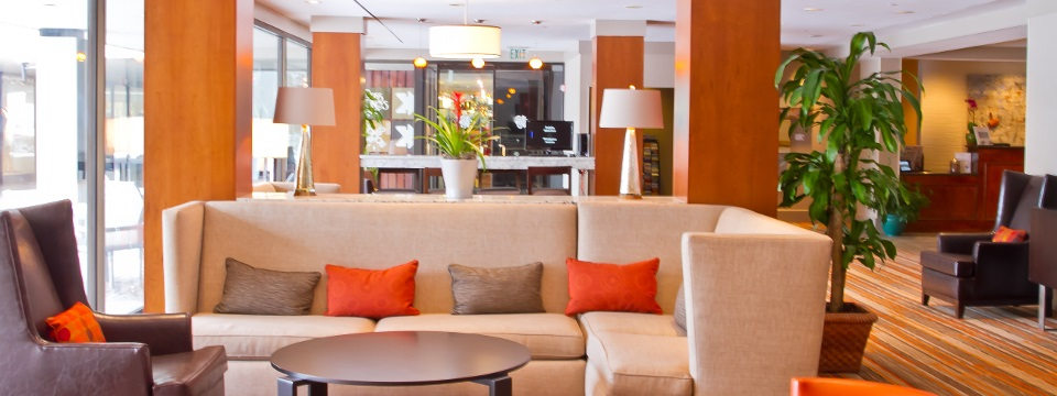 Plush white couch with orange and brown accent pillows in the hotel lobby