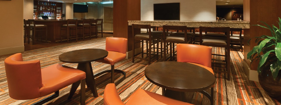 Lounge at Cross Keys hotel with orange chairs and round tables