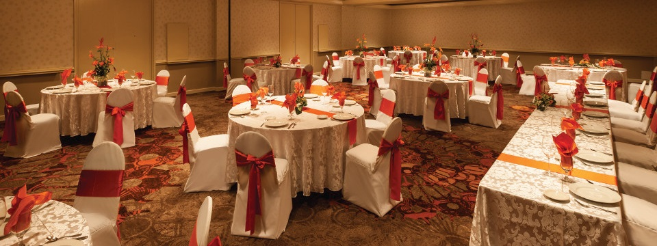 Head rectangular table and round tables with orange and white linens in the ballroom