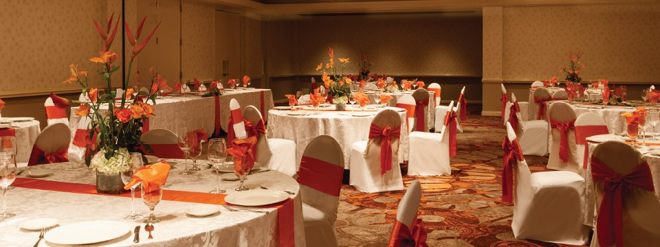 Ballroom space featuring round tables with orange and white linens