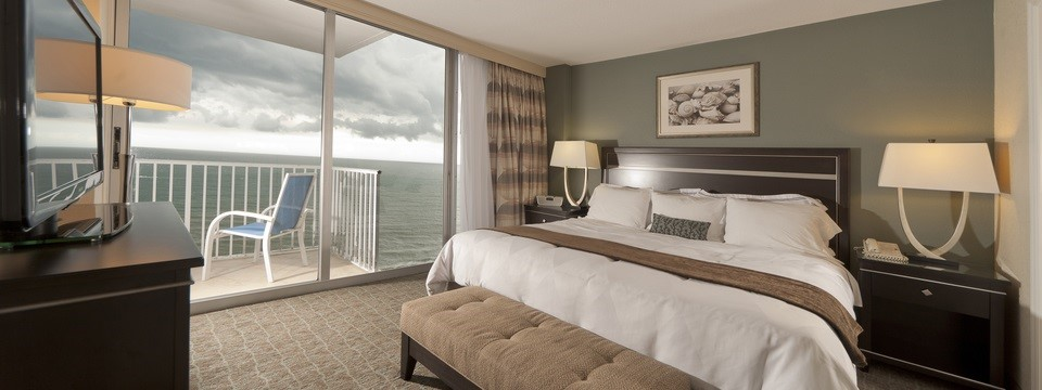 Spacious hotel room with king bed and a balcony overlooking the ocean