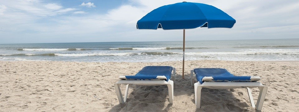 Two lounge chairs and a sun umbrella in front of the ocean
