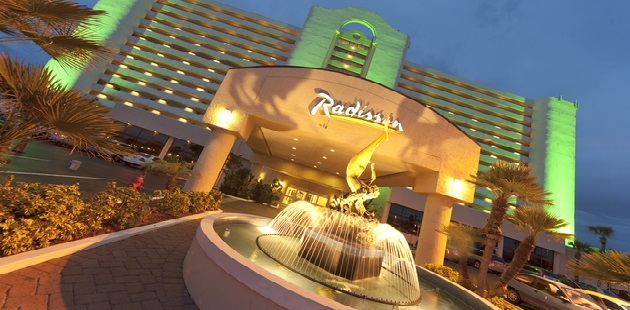 Exterior Of Radisson Suite Hotel Oceanfront At Night With Lights And Fountain