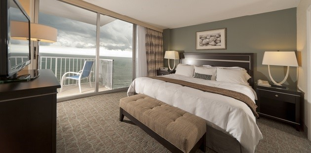 Guest room with king bed and a balcony overlooking the ocean