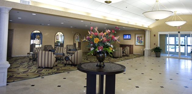 Elegant lobby with marble floor, tables, chairs and flower display