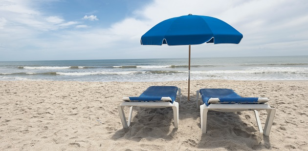 Two lounge chairs with a sun umbrella on the beach