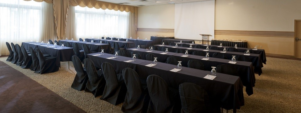 Rows of tables and chairs facing the front of the meeting room