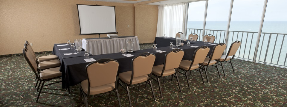 Tables aligned in a U-shape facing a white presentation screen