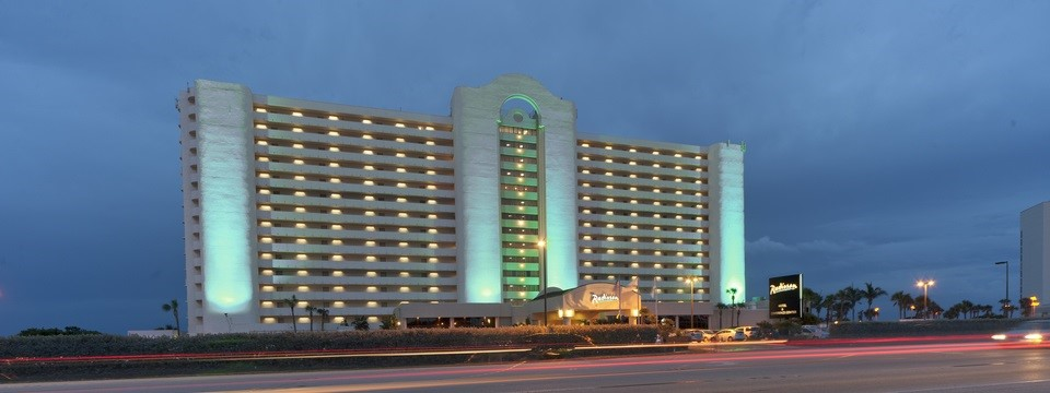 Exterior Of Radisson Suite Hotel Oceanfront Lit Up With Green Lights At Night