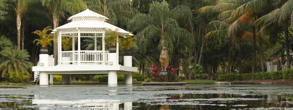 White gazebo on the water surrounded by lush vegetation