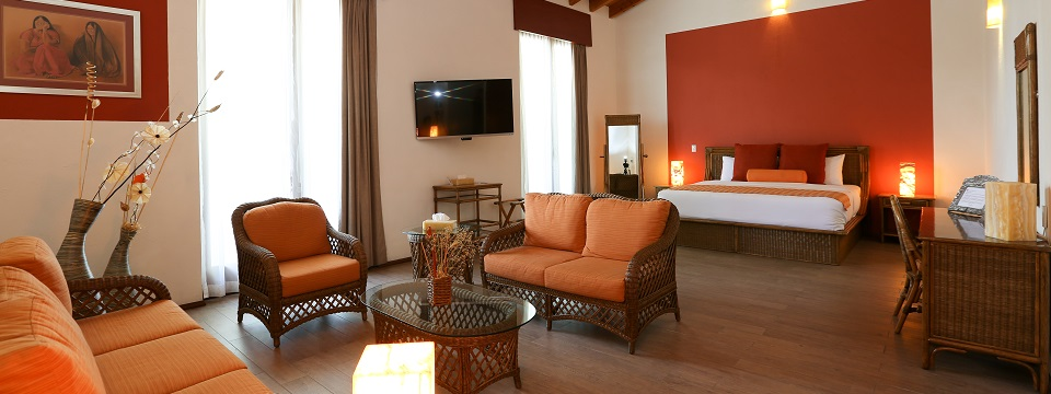 Studio-style suite with orange couch in seating area