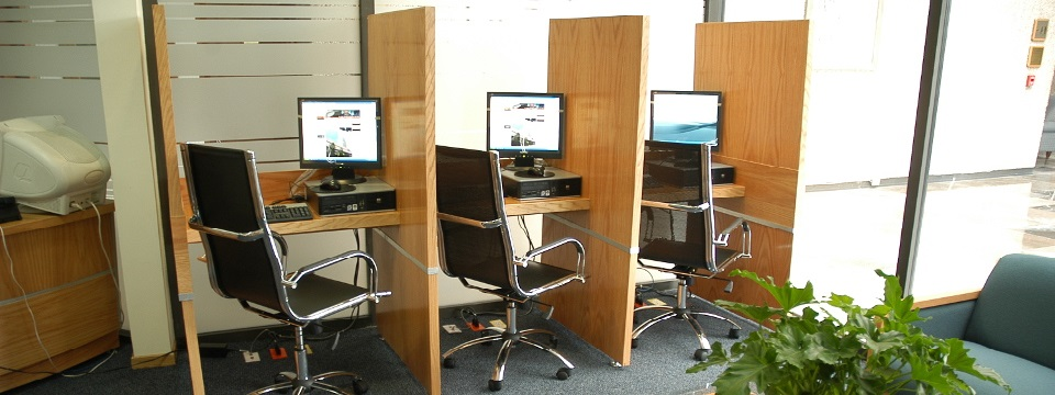Business center with three monitors and chairs separated by dividers