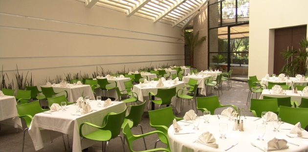 Dining area with white tables and green chairs