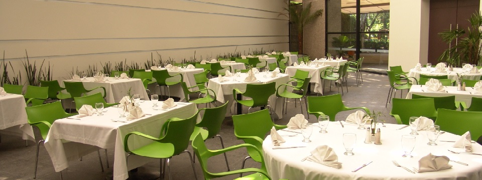 Naturally lit dining area with white tables and green chairs
