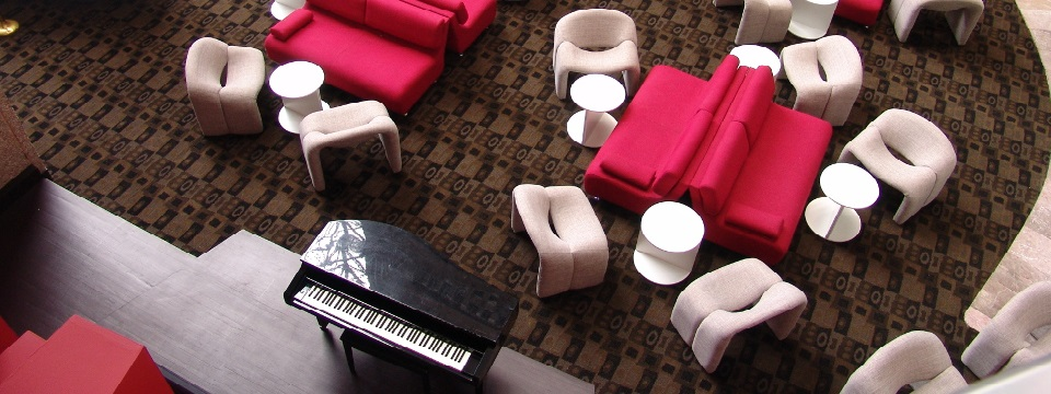 Spacious lounge with red couches, white chairs and a piano