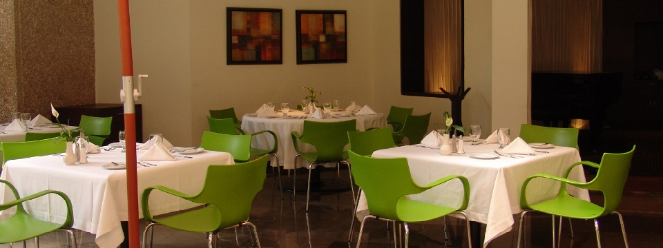 Dining area with white tables, green chairs and glassware
