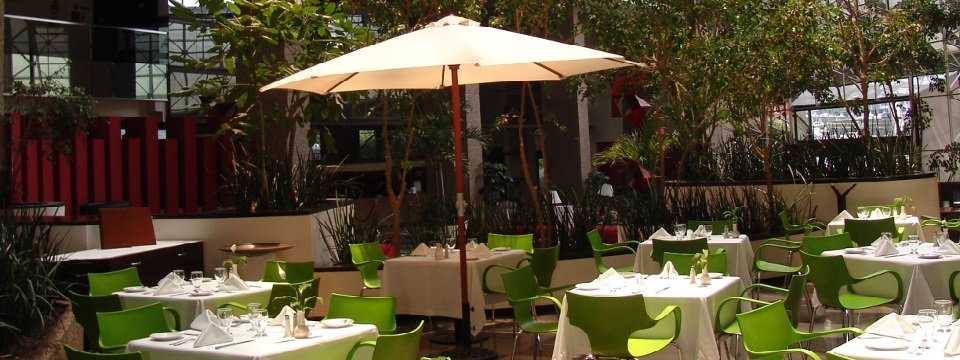 Outdoor dining area with white tables, green chairs and sun umbrellas