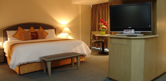 Guest suite with king bed, orange accents and flat-screen TV