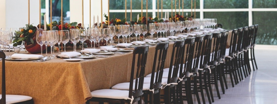 Elegant event space with a long table featuring lush green accents