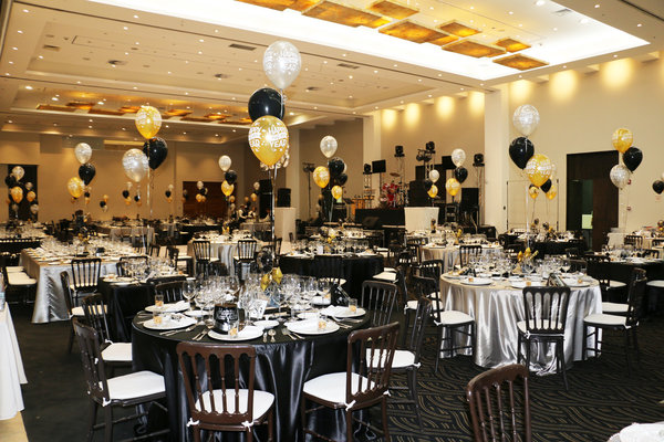 Ballroom decorated for a celebration with black and gold balloons