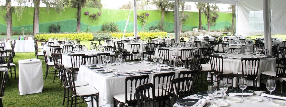 Outdoor event space with white tables and black chairs