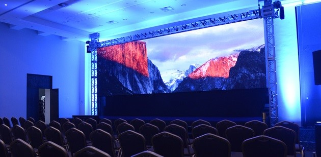 Rows of chairs facing a large presentation screen in León event space
