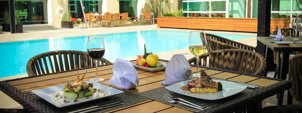 On-site dining beside the pool with meat, vegetables and wine