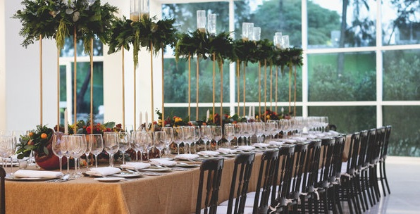 Elegant event space with long table surrounded by chairs and greenery