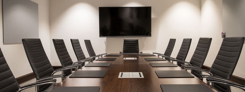 Boardroom featuring a conference table and a flat-screen TV
