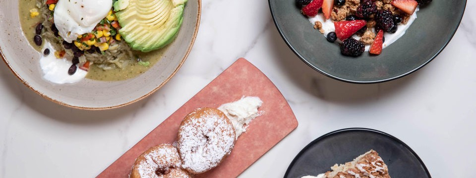 A plate of donuts, a rice dish with avocado, and a bowl of yogurt with granola and berries