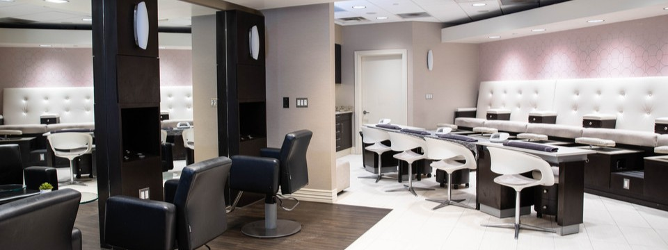Beauty salon with soft pink walls and stations for hair and nail services