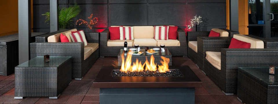 Outdoor furniture and a firepit on our Roseville hotel's patio