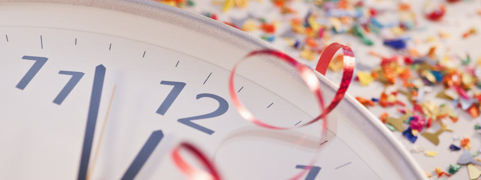 Confetti and ribbons surrounding a clock about to strike midnight