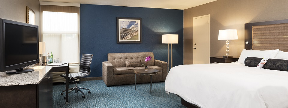 Hotel suite with a flat-screen TV, work desk and loveseat