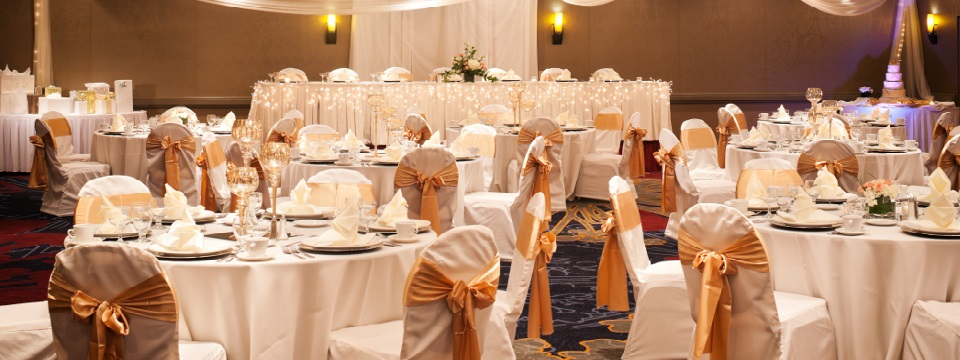 Elegant ballroom featuring round tables and rectangular head table