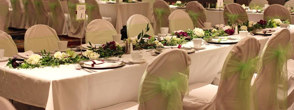 Tables set with floral centerpieces with lime-green accent bows